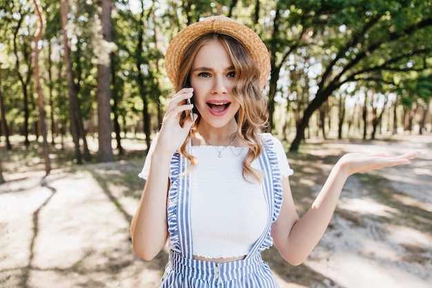 Blondes mädchen im lässigen t-shirt, das emotional am telefon spricht. außenporträt der lustigen lockigen frau, die mit smartphone auf bäumen aufwirft. Kostenlose Fotos