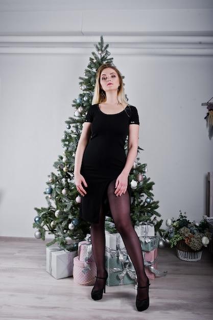 Blondes mädchen im schwarzen kleid warf nahe baum des neuen jahres mit weihnachtsgeschenkdekor im reinraum auf. Premium Fotos