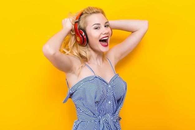 Blondes mädchen in der blauen gestreiften bluse mit kopfhörern Premium Fotos