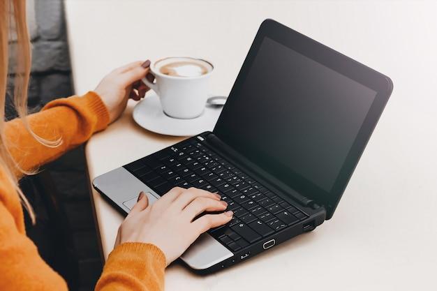 Blondes mädchen in einem café mit einem laptop und einem kaffee. freiberufler des jungen mädchens, der an einem laptop arbeitet Premium Fotos