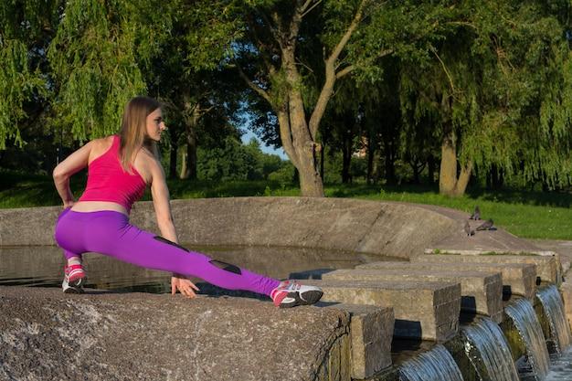 Blondes mädchen mit einer sportlichen figur in einem rosa oberteil und lila leggings macht übungen im park Premium Fotos