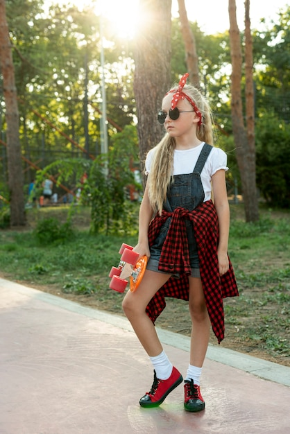 Blondes mädchen mit sonnenbrille und skateboard Kostenlose Fotos