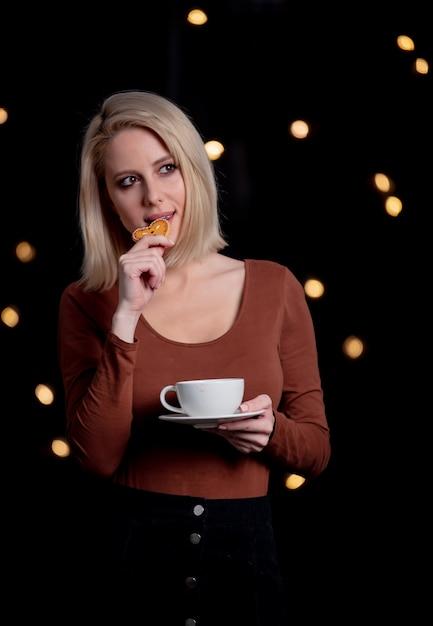 Blondes mädchen mit tasse kaffee- und lebkuchenplätzchen auf wand mit lichterketten Premium Fotos