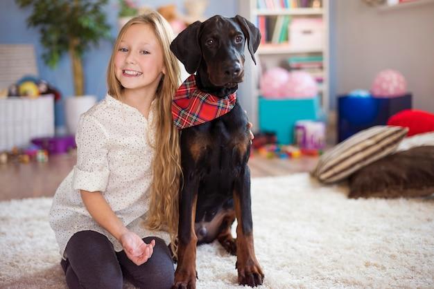 Blondes mädchen posiert mit ihrem charmanten hund Kostenlose Fotos
