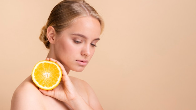 Blondes modell der nahaufnahme mit der orange aufstellung Kostenlose Fotos