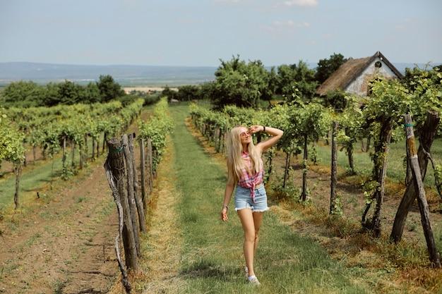 Blondes modellmädchen in jeansshorts und ärmellosem hemd, das einen sommertag im weinberg genießt. junge frau, die im modernen landschaftsstil trägt Premium Fotos