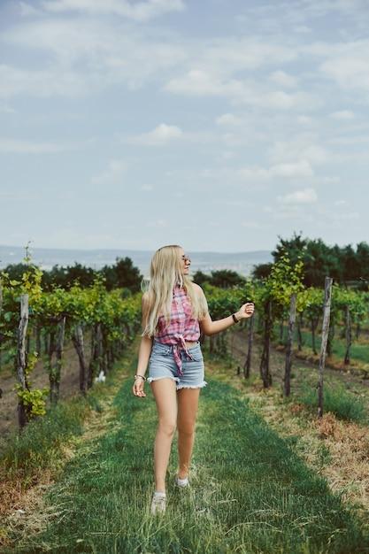 Blondes modellmädchen mit schlankem, perfektem körper in jeansshorts und ärmellosem hemd, das auf dem land geht. sommerreisen Premium Fotos