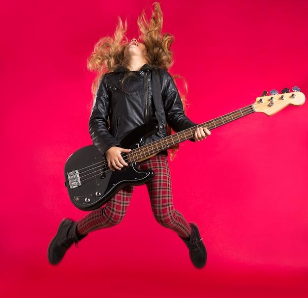 Blondes rock-and-rollmädchen mit bassgitarre springen auf rot Premium Fotos