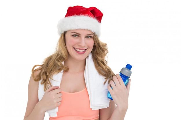 Blondine des festlichen sitzes, die flasche wasser hält Premium Fotos