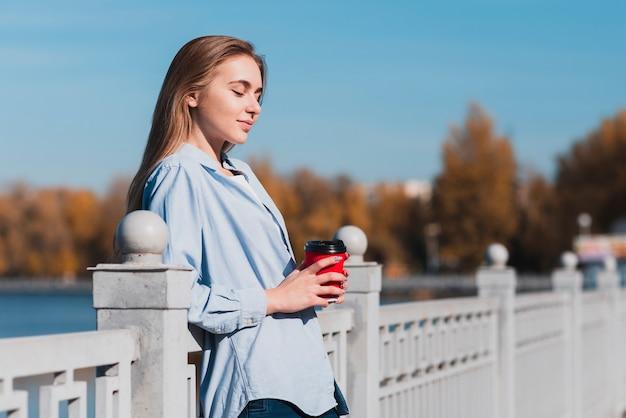 Blondine, die auf geländer stillstehen und eine kaffeetasse halten Kostenlose Fotos