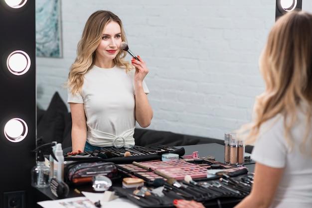 Blondine, die den rouge in spiegel setzt Kostenlose Fotos