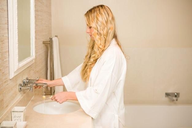 Blondine ungefähr, zum ihrer zähne im badezimmer zu hause zu putzen Premium Fotos