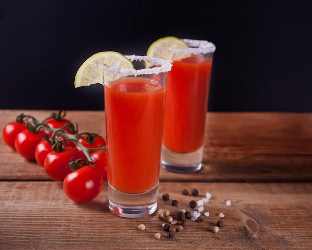 Bloody mary cocktail in gläsern. würziges getränk tomate bloody mary auf dem holztisch. Premium Fotos