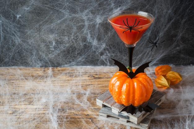 Bloody mary-cocktail, kürbis mit schlägern und spinnen für halloween, copyspace Premium Fotos