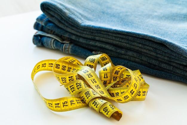 Blue jeans und messendes band auf weiß Premium Fotos
