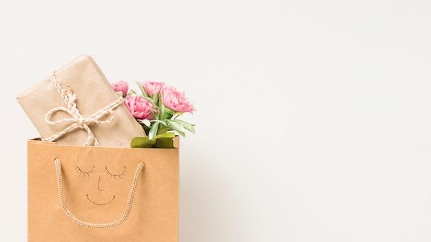 Blühen sie blumenstrauß und eingewickelte geschenkbox in der papiertüte mit dem hand gezeichneten gesicht, das auf weißem hintergrund lokalisiert wird Kostenlose Fotos