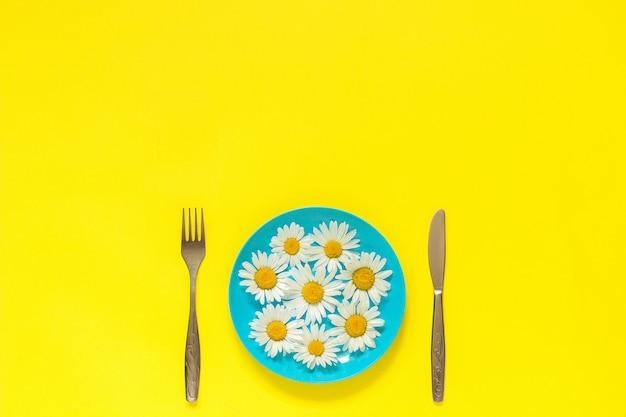 Blühen sie kamille gänseblümchen auf blauer platte, gabelmesser auf gelbem konzeptvegetarismus, diät der gesunden ernährung Premium Fotos