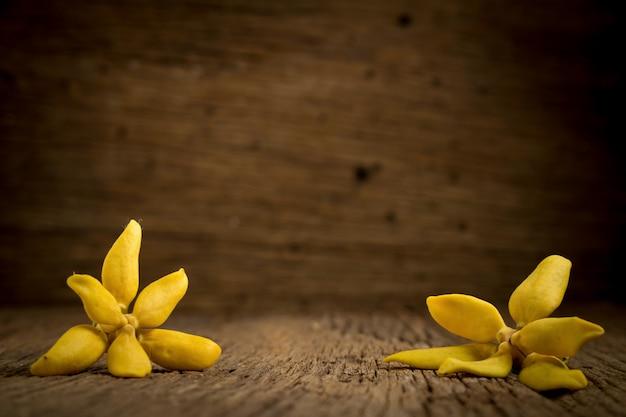 Blühen sie kletternden ylang-ylang und klettern sie ilang-ilang, manorangini, hara-champa kantali champa auf holz Premium Fotos