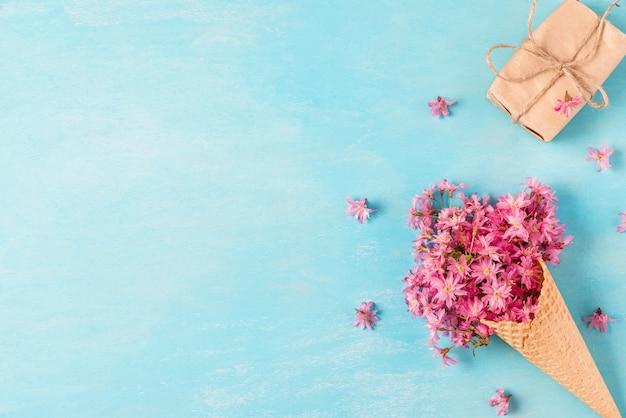 Blühende blumen der frühlingsrosa-kirsche im waffelkegel mit geschenkbox. minimales federkonzept. flach liegen Premium Fotos