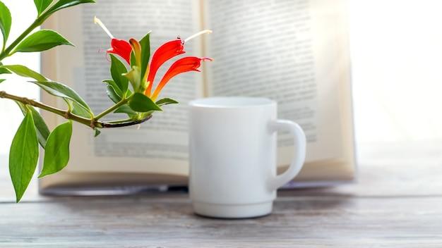 Blühende zimmerpflanze in der nähe einer tasse kaffee und eines offenen buches Premium Fotos