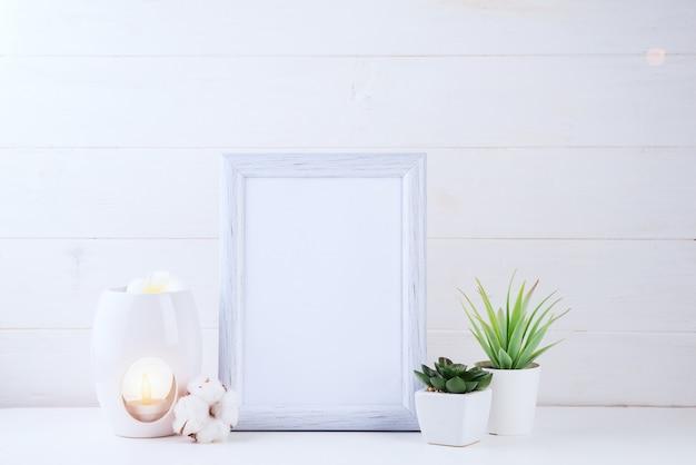 Blüht succulents, kerze und aromalampe mit einem weißen rahmen im licht, copyspace Premium Fotos