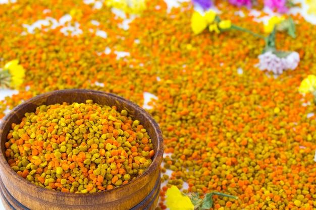 Blütenpollen in einer holzkiste. blumen liegen auf pollen Premium Fotos