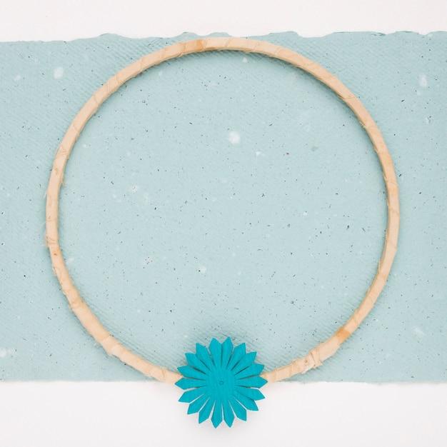 Blume auf hölzernem kreisrahmen auf blauem papier Kostenlose Fotos