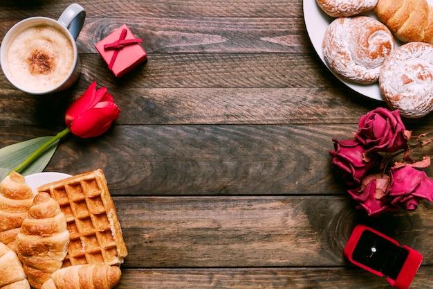 Blumen, bäckerei auf teller, ring in geschenkbox und tasse getränk Kostenlose Fotos