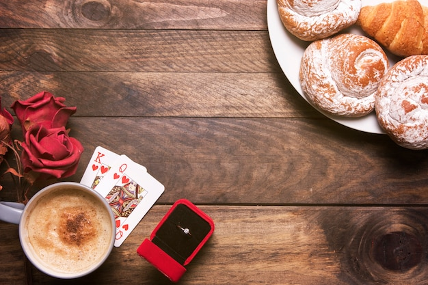 Blumen, bäckerei auf tellern, ring in geschenkbox, spielkarten und tasse getränk Kostenlose Fotos