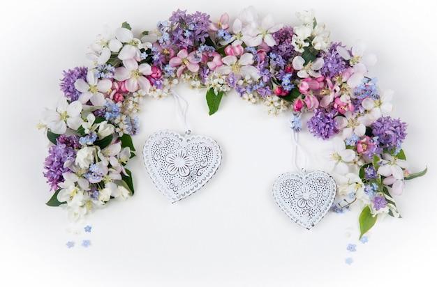 Blumen der vogelkirsche, flieder, vergissmeinnicht und apfelbäume, gesäumt von einem bogen Premium Fotos