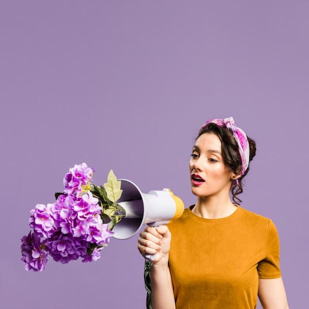 Blumen im megaphon und in der frauenunterhaltung Premium Fotos