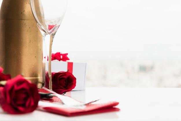 Blumen in der nähe von glas, geschenk und eine flasche zu trinken Kostenlose Fotos