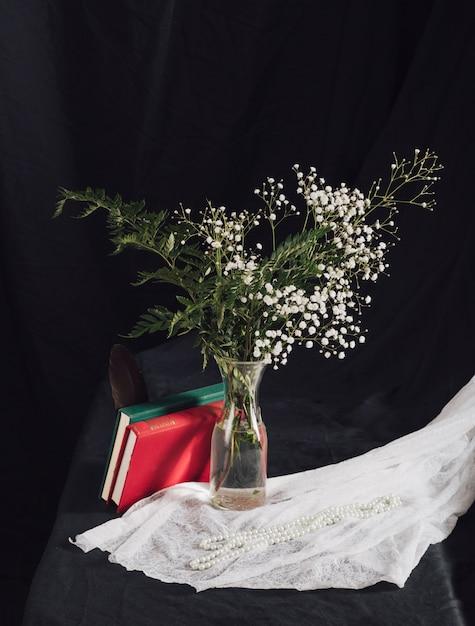 Blumen mit anlagen im vase nahe volumina und perlen auf weißem gewebe auf tabelle Kostenlose Fotos