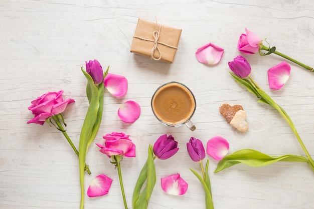 Blumen mit geschenkbox und kaffee auf dem tisch Kostenlose Fotos