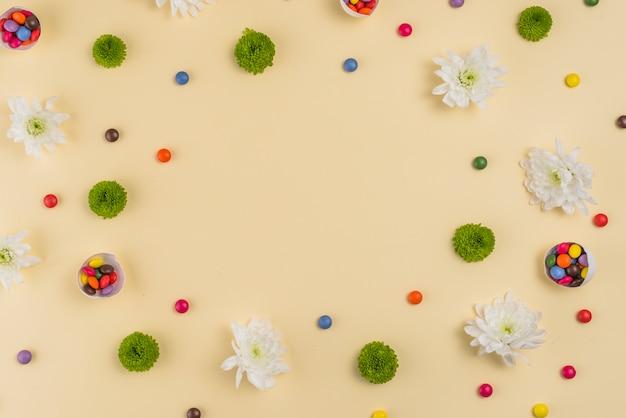 Blumen mit kleinen süßigkeiten auf dem tisch Kostenlose Fotos