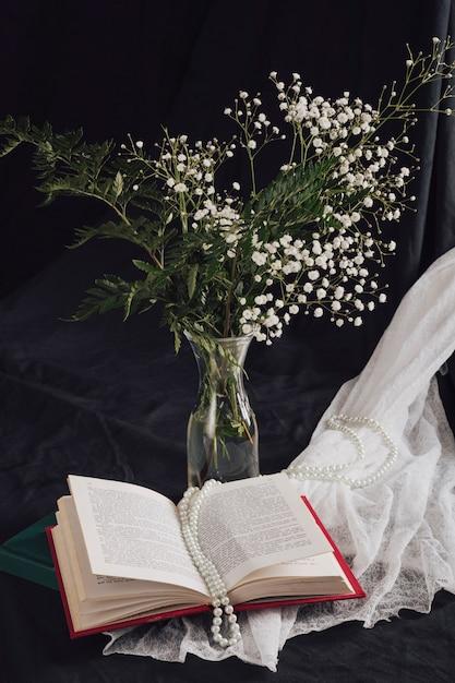 Blumen mit pflanzen im vase nahe volumen und perlen auf weißem gewebe Kostenlose Fotos