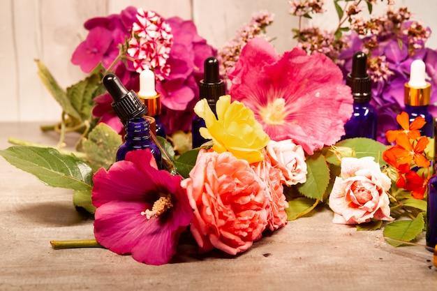 Blumen und flaschen ätherische öle für die aromatherapie Premium Fotos