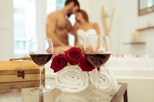 Blumen und gläser trinken nahe den paaren, die im whirlpool küssen Kostenlose Fotos