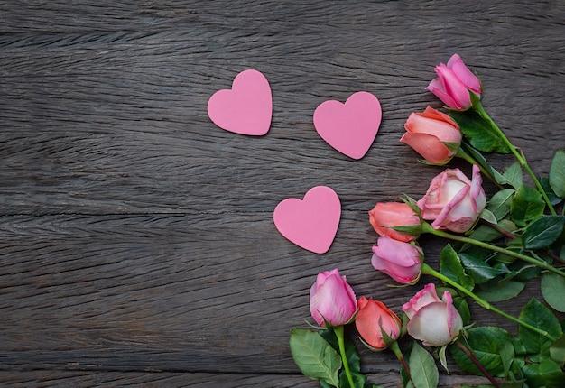 Blumen und herzen auf einem hölzernen hintergrund. rosen und platzende herzen auf einer dunklen holzoberfläche Premium Fotos