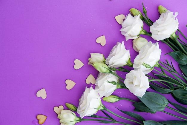 Blumen und herzen auf einem lila hintergrund. . für glückwünsche leer. Premium Fotos