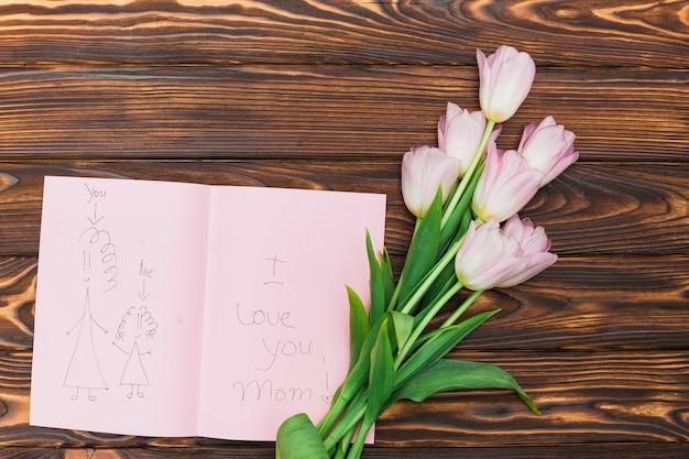Blumen und kinderzeichnung mit text ich liebe dich mutter auf hölzerner tabelle Kostenlose Fotos