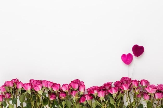 Blumen zusammensetzung. rote rosen auf weißem hölzernem hintergrund. flache lage, draufsicht. Premium Fotos