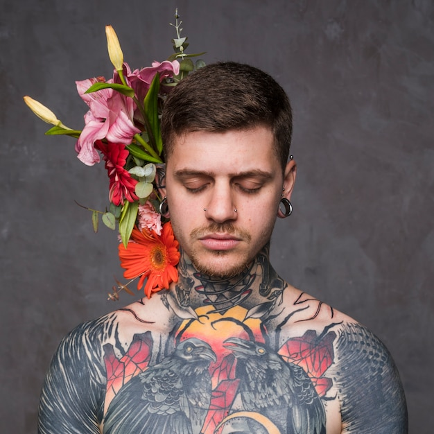 Blumendekoration hinter dem tätowierten und durchbohrten jungen mann gegen grauen hintergrund Kostenlose Fotos