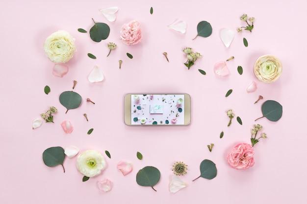 Blumengesteck mit einem handy in einem blumenrahmen, in einer draufsicht und in einer ebenenlage Premium Fotos