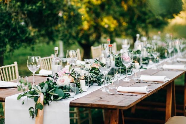 Blumengirlande aus eukalyptus und rosa blumen liegt auf dem tisch Kostenlose Fotos