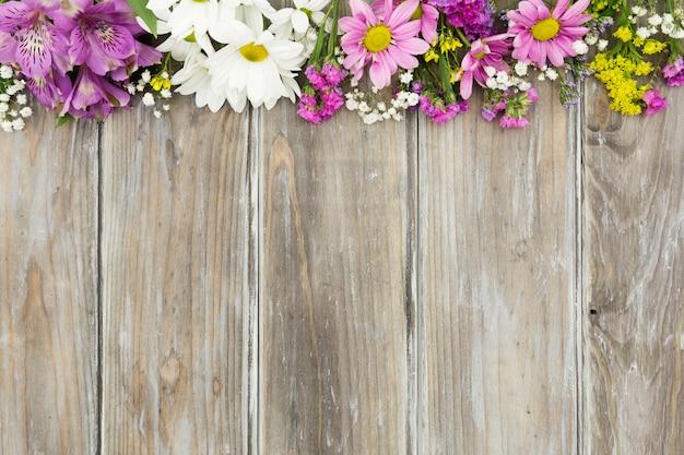 Blumenrahmen der draufsicht mit hölzernem hintergrund Kostenlose Fotos