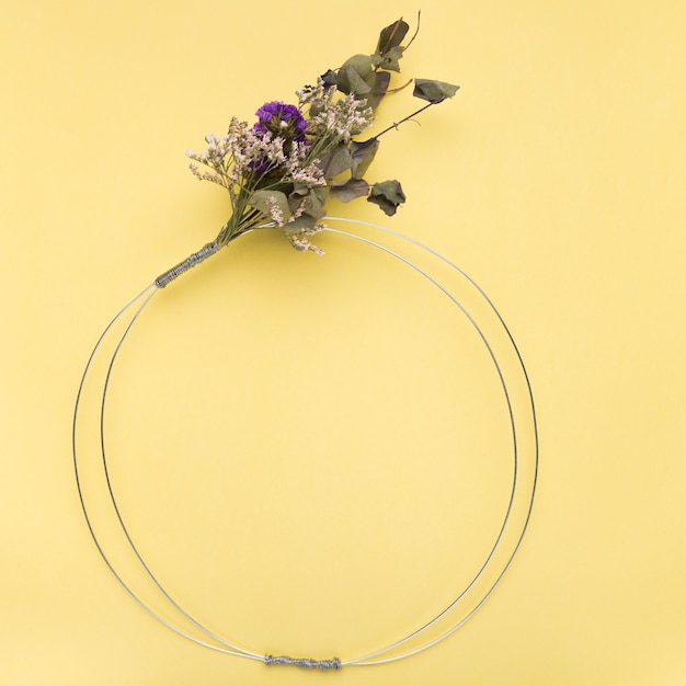 Blumenstrauß auf leerem metallischem ring über dem gelben hintergrund Kostenlose Fotos