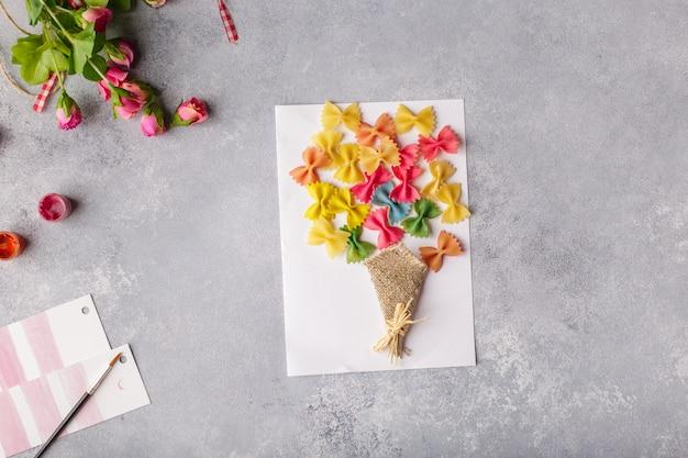 Blumenstrauß aus farbigem papier und farbigen nudeln. Premium Fotos