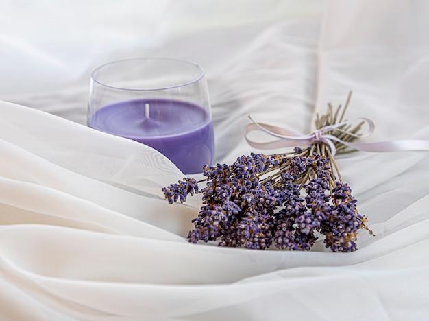 Blumenstrauß aus getrocknetem lavendel, gebunden mit einem band und der duftkerze aus lavendel liegt auf einem weißen, luftigen stoff. tiefenschärfe mit geringer schärfentiefe. harmonie. Premium Fotos