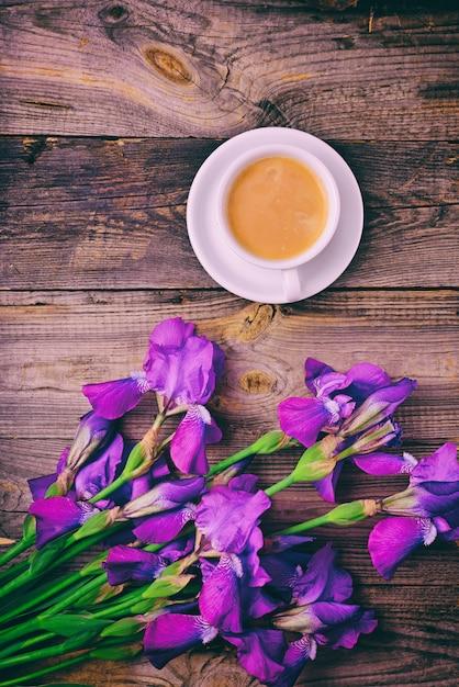 Blumenstrauß aus iris und einer tasse kaffee Premium Fotos